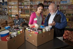 woman assisting a man with a box of food pantry items