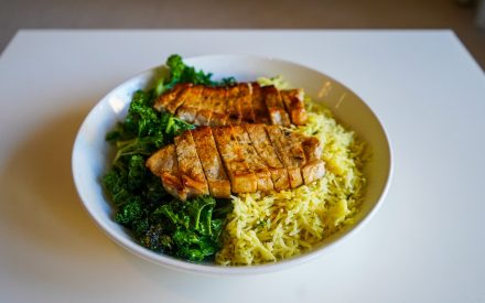 a plate of chicken rice and green vegetables