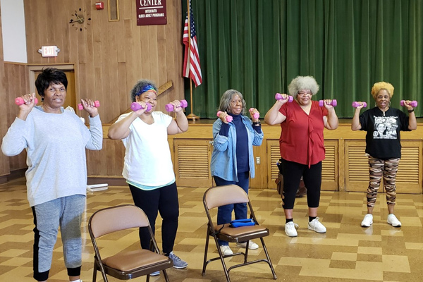 four women lift small weights during a class