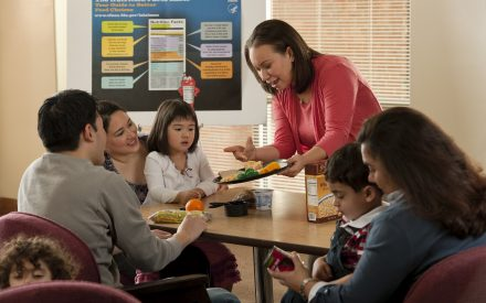 Parents and a teacher introducing toddlers to new foods including broccoli