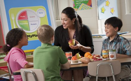 A woman teaching three young children about healthy foods