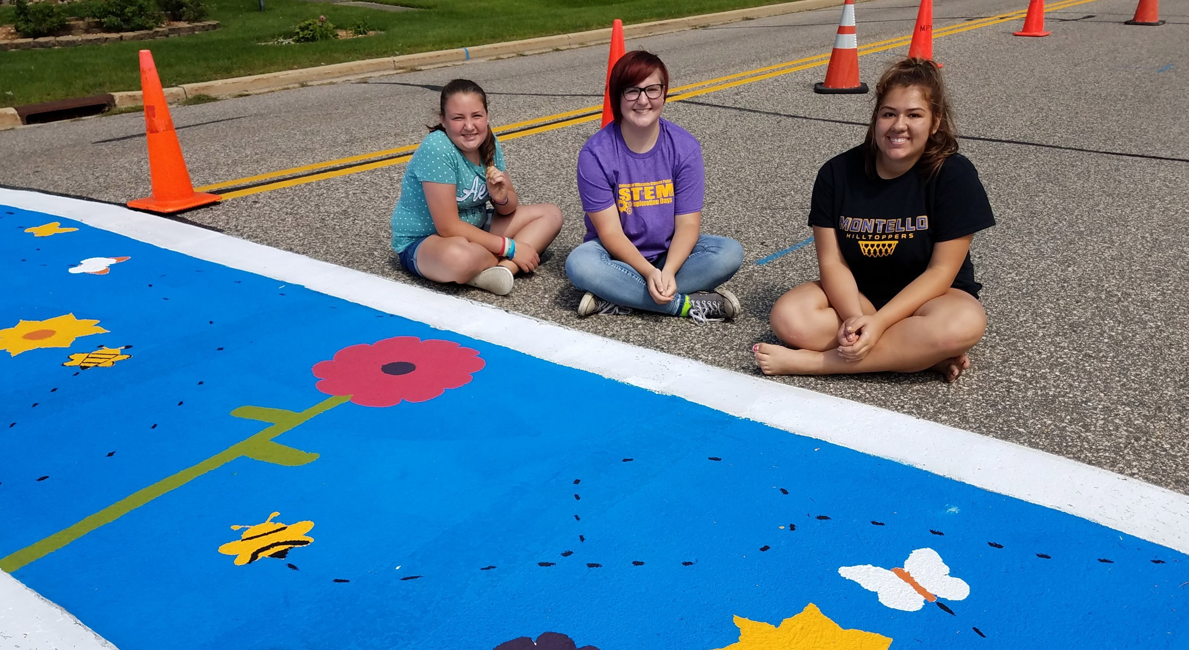 Three teens sit by the crosswalk they painted bright blue and decorated with flowers.
