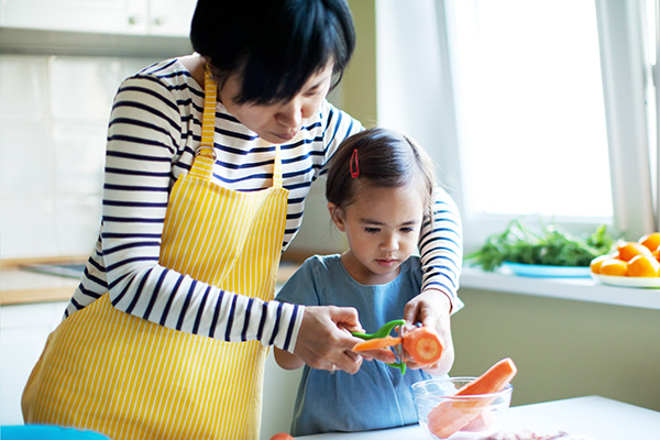 Mom and a little girl cutting a carrot.