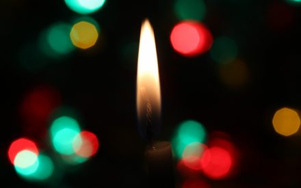Green, red and gold lights around a flame